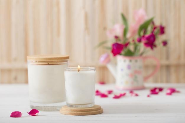 Velas aromáticas com flores na parede de madeira