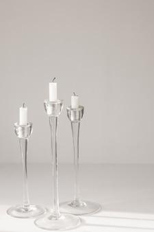 Velas brancas em castiçais de vidro em um fundo branco design ou decoração de interiores
