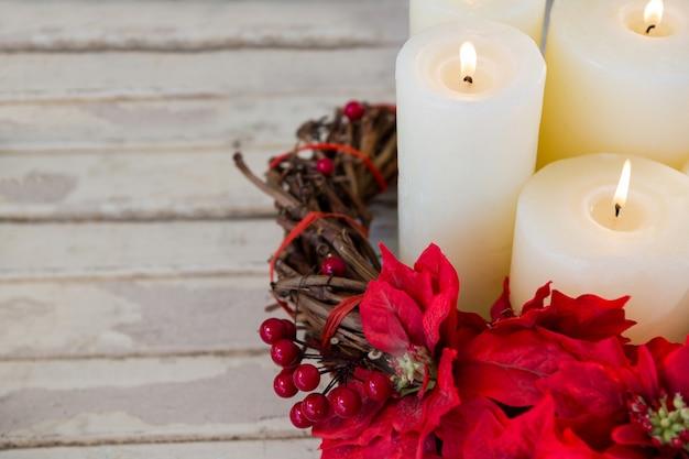 Velas brancas iluminadas com flores vermelhas