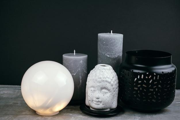Velas cinza, lâmpada redonda branca e cabeça de buda de cerâmica branca em uma mesa em frente à parede preta