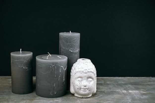 Velas cinzas e cabeça de buda de cerâmica branca em uma mesa em frente a parede preta