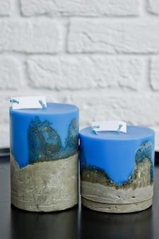 Velas coloridas caseiras com concreto na superfície de uma parede branca