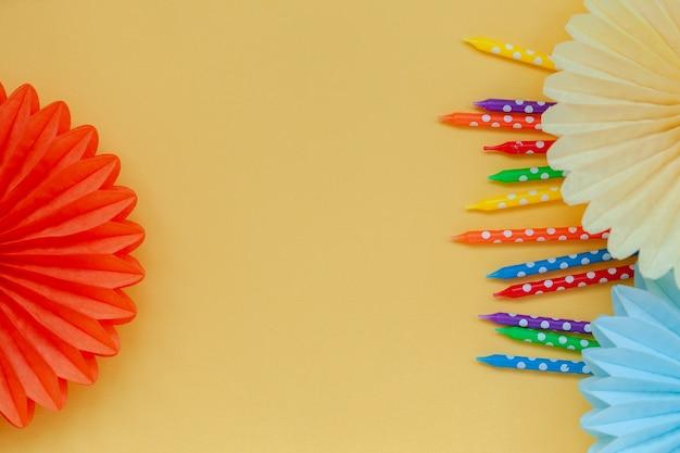 Velas coloridas de aniversário festivo e leques de papel em amarelo pastel ou festa