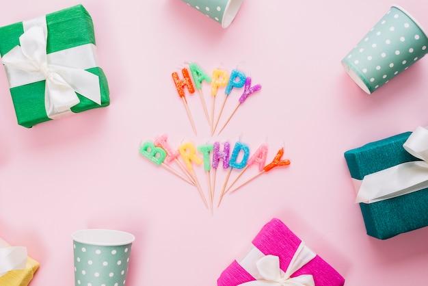 Velas coloridas do feliz aniversario cercadas com caixas de presente e vidros descartáveis no fundo cor-de-rosa