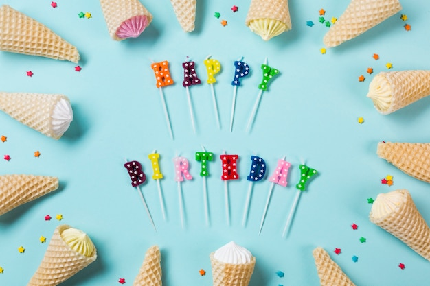 Velas coloridas do feliz aniversario decoradas com aalaw em cones do waffle no contexto azul
