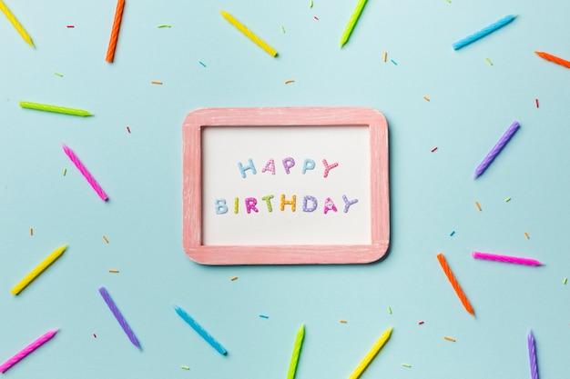 Velas coloridas e polvilha espalhar em torno da moldura branca feliz aniversário em fundo azul