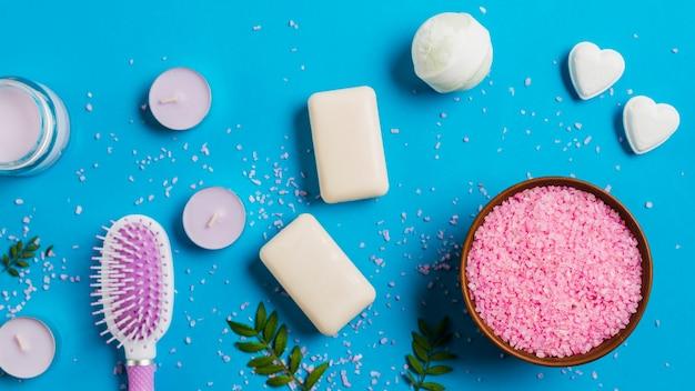 Velas com sabão; bomba de banho; escova de cabelo e rosa sal no pano de fundo azul