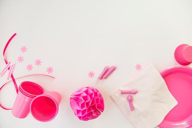 Velas cor-de-rosa; copos de plástico; lenco de papel; placas e bola de papel de favo de mel no fundo branco