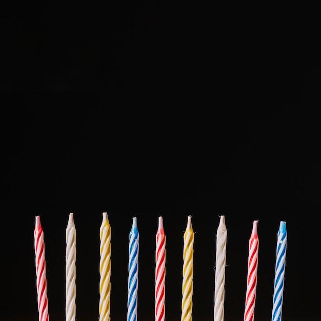 Velas de aniversário colorido listrado contra fundo preto