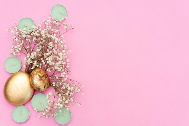 Velas de hortelã no fundo rosa, flores secas e folha de ouro