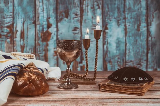 Velas de mesa de véspera do shabat e copo de vinho com pão chalá coberto,