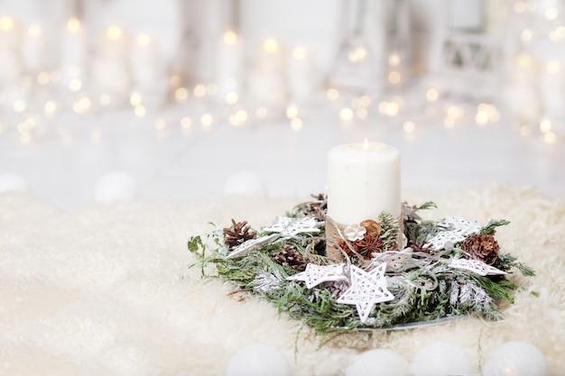 Velas de natal e ramos de abeto nevado sobre fundo branco com luzes. decoração de ano novo com uma árvore do abeto em tons de branco.
