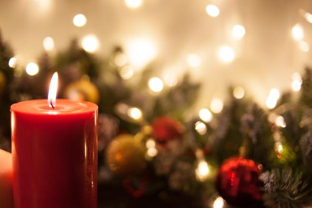 Velas de natal em galhos de uma árvore de natal e guirlandas brilhantes