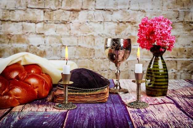 Velas de shabat em castiçais de pão chalá para shabat com vinho em um copo