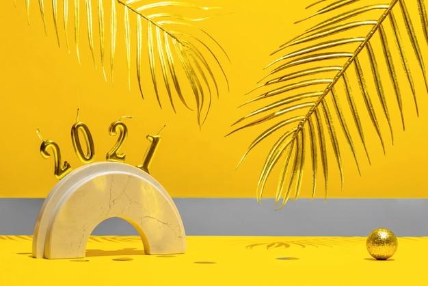 Velas douradas com o ano novo 2021 no arco de mármore, folhas de palmeira, confetes em um fundo amarelo