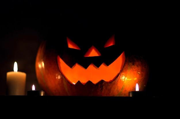 Velas e abóbora para o halloween em fundo escuro. foto com espaço de cópia