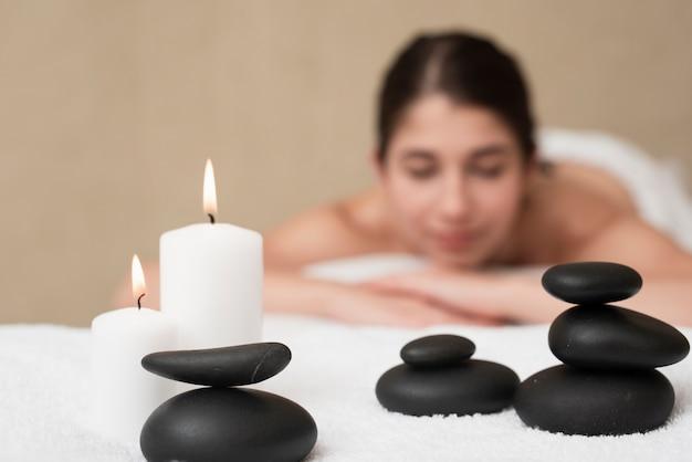 Velas e pedras de spa com mulher no spa