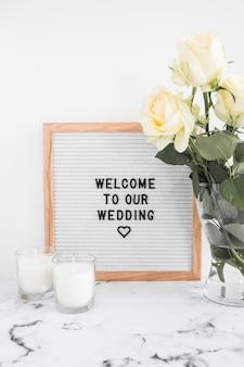 Velas e vaso com placa de boas vindas para casamento contra o pano de fundo branco
