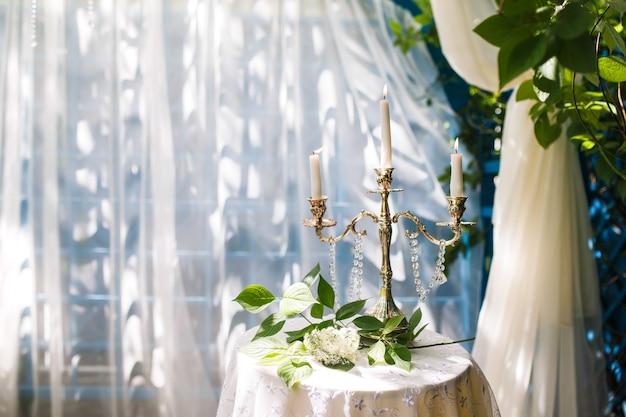 Velas em castiçais em cima da mesa. um galho de árvore fica a seguir. decoração do casamento.
