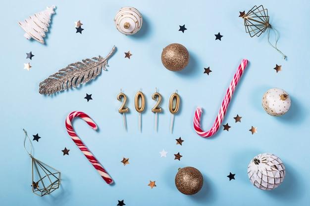 Velas em forma de figuras 2020 entre as decorações de natal em um fundo azul