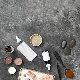 Velas; garrafa de óleo essencial; barro de rhassoul; último; sal-gema do himalaia na bandeja contra o pano de fundo preto concreto