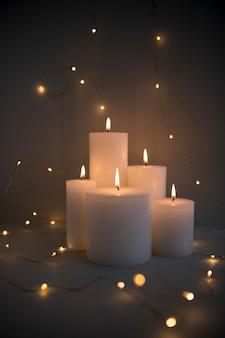 Velas iluminadas cercadas com luzes de fadas brilhantes no fundo escuro