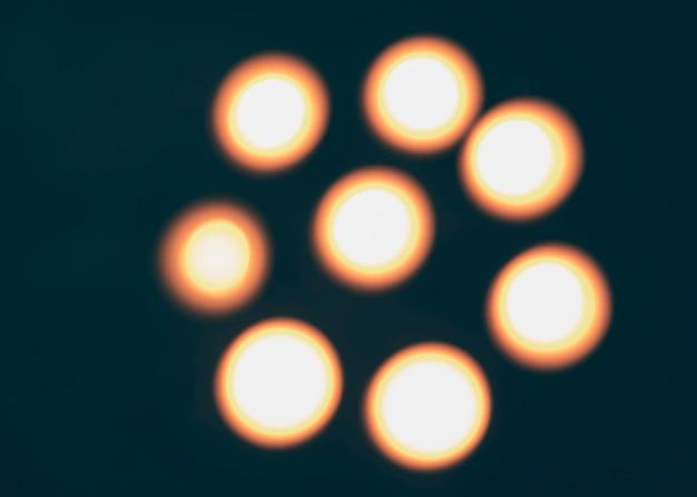 Velas iluminadas desfocadas em pano de fundo escuro