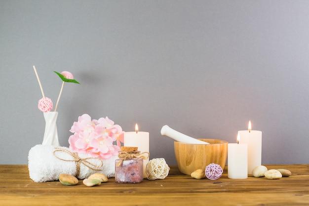 Velas iluminadas; esfregue garrafas; flor; pedras de spa; almofariz e pilão na mesa de madeira