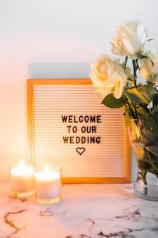 Velas iluminadas perto da placa de boas-vindas de casamento e vaso contra o pano de fundo branco