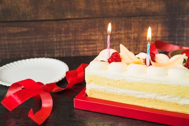 Velas iluminadas sobre o bolo com fita vermelha e placa na mesa de madeira