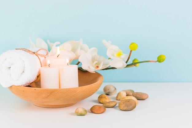 Velas iluminadas; toalhas; pedras de flor e spa na superfície branca