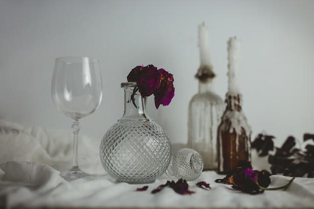 Velas nas garrafas ao lado de um vaso com uma flor dentro e um copo