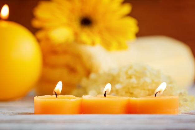 Velas pequenas amarelas do close up. configuração de produtos de spa