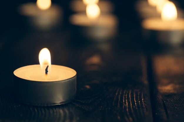 Velas queimando na escuridão sobre preto. conceito de comemoração.