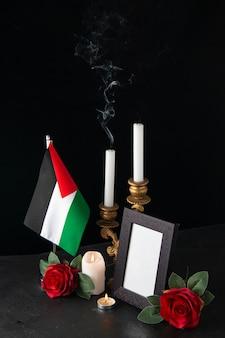 Velas sem fogo com bandeira palestina e flores na superfície escura