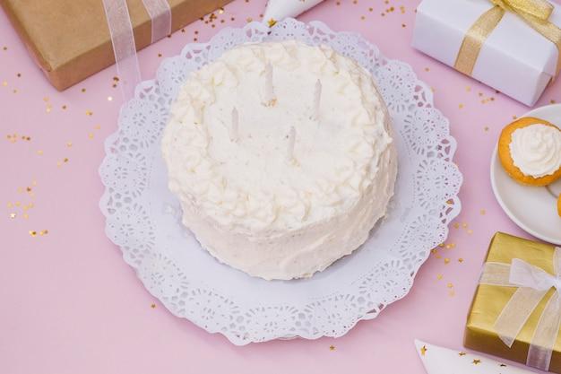 Velas sobre o bolo de aniversário branco e presentes no pano de fundo rosa