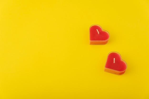 Velas vermelhas em forma de coração em amarelo