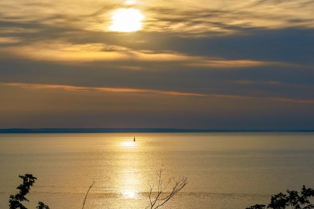 Veleiro à distância ao pôr do sol no oceano