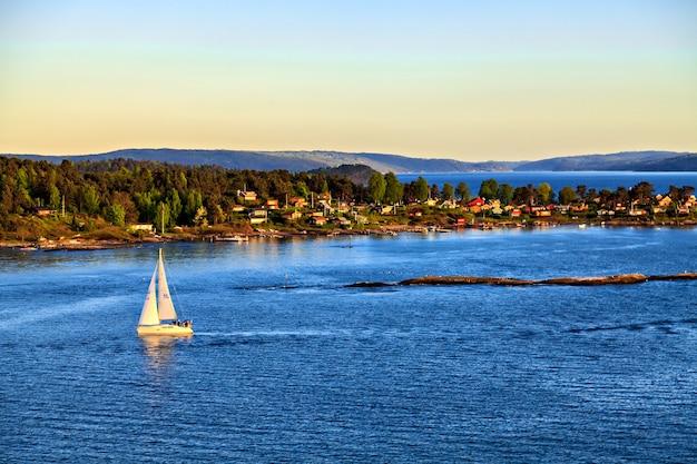 Veleiro ao largo da costa com vista da cidade e das montanhas