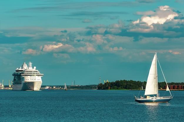 Veleiro azul viajando contra o navio de cruzeiro em riga