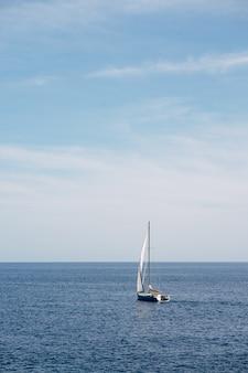 Veleiro branco flutua em mar aberto