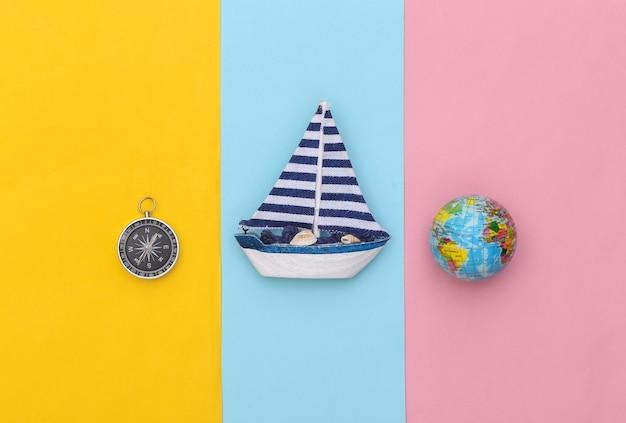 Veleiro, bússola e globo em um fundo colorido. conceito de viagens do minimalismo. vista do topo. postura plana