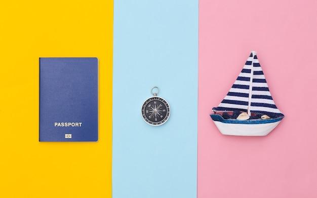Veleiro, bússola e passaporte em um fundo colorido. conceito de viagens do minimalismo. vista do topo. postura plana