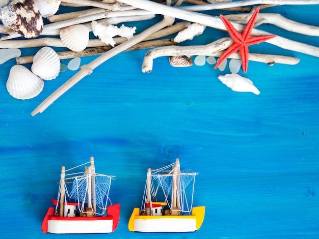 Veleiro de brinquedo, madeiras resistidas, rede e conchas na parede de madeira azul perto com espaço de cópia