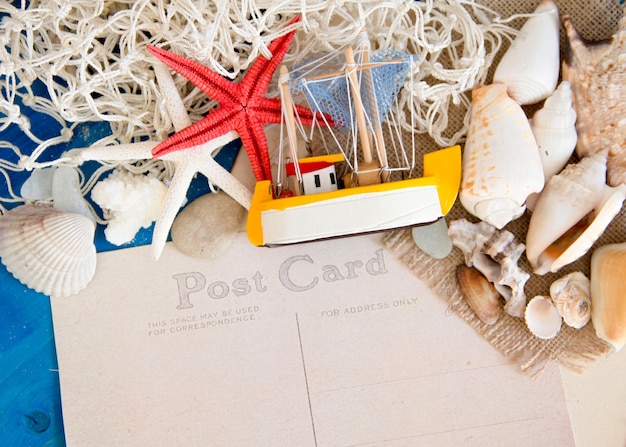 Veleiro de brinquedo, rede e conchas na parede de madeira azul perto com espaço de cópia em papel cartão postal