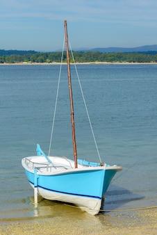Veleiro de pesca azul de madeira ancorado perto da costa