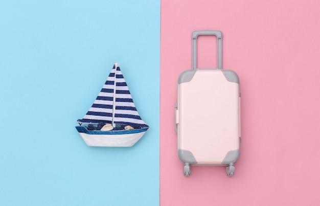 Veleiro e bagagem de viagem em um fundo rosa azul. conceito de minimalismo de viagens. vista do topo. postura plana