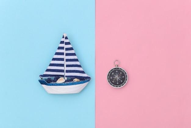 Veleiro e bússola em um fundo rosa azul. viagens, conceito de minimalismo. vista do topo. postura plana