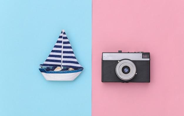 Veleiro e câmera em um fundo rosa azul. viagens, conceito de minimalismo. vista do topo. postura plana