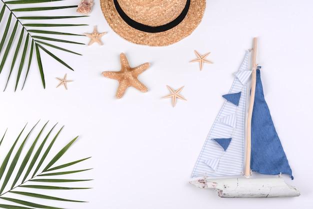 Veleiro e chapéu com conchas e estrelas do mar em um fundo branco. fundo de verão